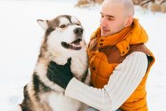 Équipez la marche avec l'horaire d'hiver de chien avec la neige dans l'amitié de Malamute de forêt Photos libres de droits