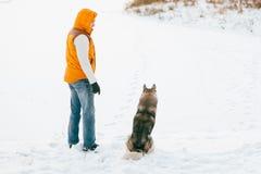 Équipez la marche avec l'horaire d'hiver de chien avec la neige dans l'amitié de Malamute et de chiens de traîneau de forêt Images stock