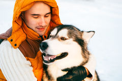 Équipez la marche avec l'horaire d'hiver de chien avec la neige dans l'amitié de Malamute et de chiens de traîneau de forêt Photo stock