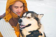 Équipez la marche avec l'horaire d'hiver de chien avec la neige dans le Malamute de forêt Images stock