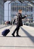 Équipez la marche avec le sac et le téléphone portable à la station Image stock