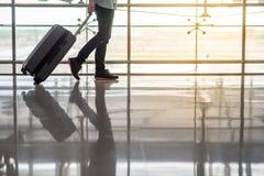 Équipez la marche dans le terminal d'aéroport avec le bagage Image stock