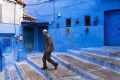 Équipez la marche dans une rue de la ville de Chefchaouen au Maroc Images libres de droits