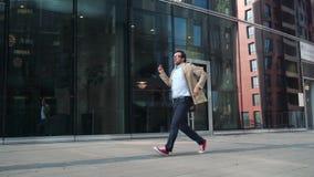 Équipez la marche et la danse près du bâtiment en verre moderne clips vidéos