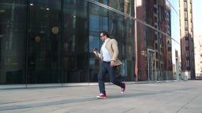 Équipez la marche et la danse près du bâtiment en verre moderne banque de vidéos