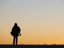 Équipez la marche le long de la route, éclairée à contre-jour au coucher du soleil Photo stock