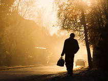 Équipez la marche le long de la route, éclairée à contre-jour au coucher du soleil Photographie stock