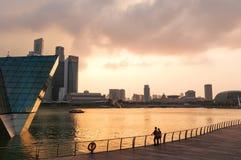 Équipez la marche sur la promenade dans le soleil de soirée avec l'horizon de Photographie stock libre de droits