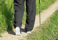 Équipez la marche sur les espadrilles de port de chemin arénacé, utilisant dépister des bâtons Photographie stock libre de droits