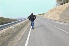 Équipez la marche sur une route de montagne à son rêve Images libres de droits