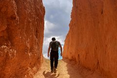 Équipez la marche vers le ciel dans une allée de roche rouge/orange photos stock