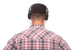 Équipez la musique de écoute avec des écouteurs en fonction Photo stock