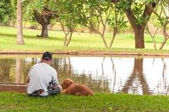 Équipez la pêche dans le lac à côté de son chien d'ami Image libre de droits