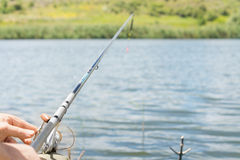 Équipez la pêche sur un lac avec une bobine et une tige de rotation Images stock