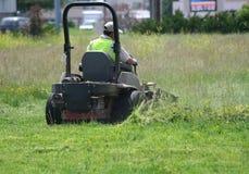 Équipez la pelouse de fauchage avec un tour sur la tondeuse à gazon Photographie stock libre de droits