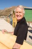 Équipez la planche de surf de transport tout en se tenant contre des huttes de plage Photographie stock libre de droits