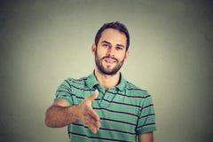 Équipez la poignée de main de offre d'isolement sur le fond gris de mur Images stock
