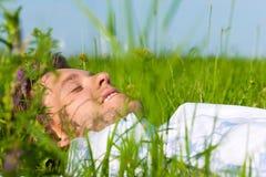 Équipez la pose sur une pelouse et rêvez Photographie stock libre de droits
