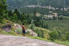 Équipez la position à une roche dans la forêt verte Image stock