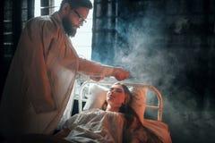 Équipez la position contre la femme malade dans le lit d'hôpital Photo stock