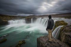 Équipez la position près du bord de la cascade de Godafoss image stock
