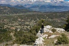 Équipez la position sur des roches et appréciez la vue essoufflée image stock