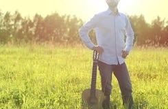 Équipez la position sur la guitare acoustique de champ et de participation d'été Copiez l'espace Concept extérieur de festival d' Photo stock