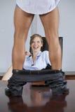 Équipez la position sur la table avec le pantalon vers le bas, en flirtant avec la femme d'affaires dans le bureau Image libre de droits