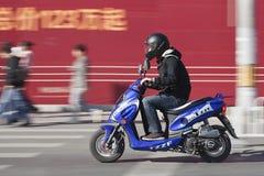 Équipez la précipitation sur un scooter avec le panneau d'affichage sur le fond, Pékin, Chine Photo stock