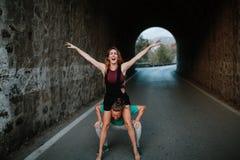 Équipez la préparation pour porter son amie sur ses épaules La femme soulève des bras et rire excités Photographie stock