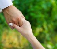 Équipez la prise des doigts d'une femme par la main Image stock