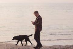 Équipez la promenade avec le chien et le service de mini-messages sur le téléphone portable Photographie stock libre de droits