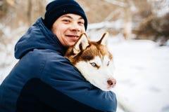 Équipez la promenade avec son chien rouge de chien de traîneau sibérien d'ami en parc neigeux toned photos stock