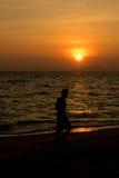 Équipez la promenade sur la plage le temps de coucher du soleil Photo stock