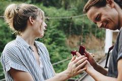 Équipez la proposition à son amie heureuse dehors aiment et à concept de mariage Photo stock