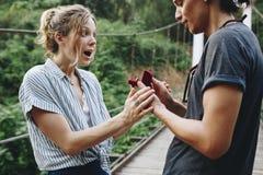 Équipez la proposition à son amie heureuse dehors aiment et à concept de mariage Image libre de droits