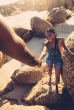 Équipez la roche s'élevante de aide de femme à la plage Photos stock
