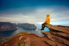 Équipez la séance de touristes sur le bord d'une roche photo stock