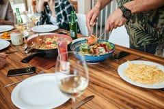 Équipez la salade et le dîner végétaux de mélange de avoir avec des amis Photos libres de droits