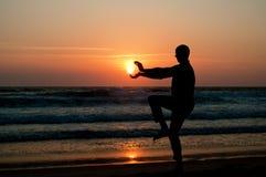 Équipez la silhouette prenant le soleil sur la plage au coucher du soleil Image libre de droits