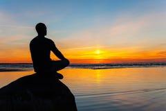Équipez la silhouette se reposant sur la pierre au bord de la mer contemplant le soleil photos libres de droits