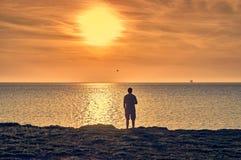 Équipez la silhouette se tenant sur une plage et observant un lever de soleil Photo stock
