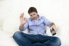 Équipez la télévision de observation au sofa de salon avec le signe correct donnant de sourire à télécommande de main Image stock