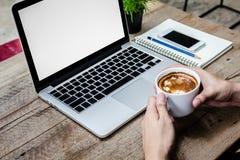 Équipez la tasse de café de prise avec l'ordinateur portable sur la table en bois Image libre de droits