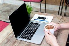 Équipez la tasse de café de prise avec l'ordinateur portable sur la table en bois Photo stock