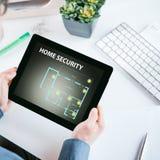Équipez la vérification sa sécurité à la maison sur son comprimé Images libres de droits