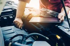 Équipez la vérification un moteur de voiture et tenez la recherche de comprimé des données photographie stock