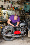 Équipez la vieille moto de réparation dans le garage, sur le fond des outils et de l'équipement Images stock