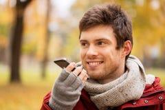 Équipez la voix d'enregistrement sur le smartphone au parc d'automne photographie stock
