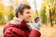 Équipez la voix d'enregistrement sur le smartphone au parc d'automne images stock